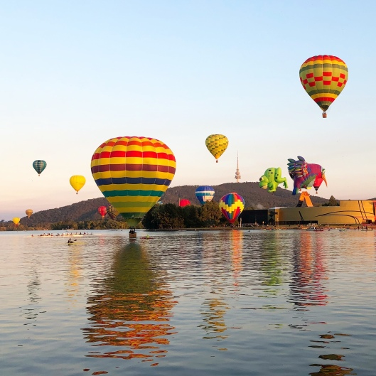 Balloons skimming water of Lake Burley Griffin during Canberra Balloon Spectacular