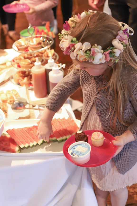 Small girl taking food from high tea buffet