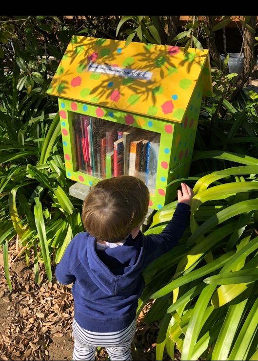 Image of toddler opening door of little street library
