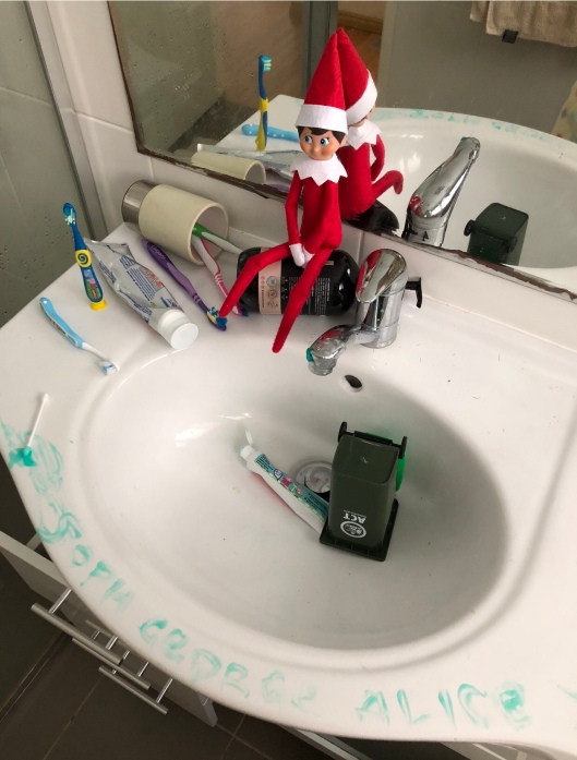 Christmas elf on a shelf writing with toothpaste