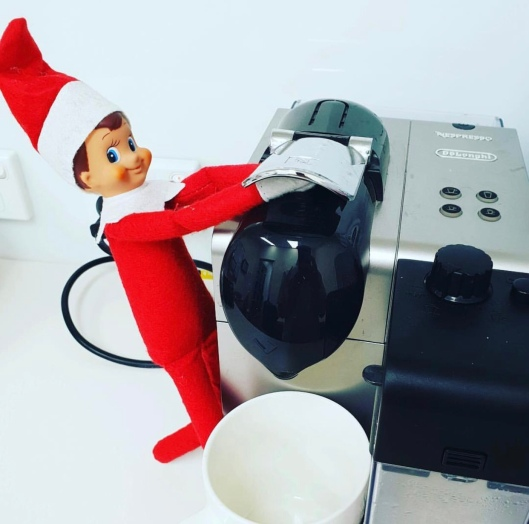 Christmas elf on a shelf making coffee