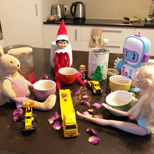 Ben the elf having a Christmas tea party with Barbie and the other toys on the kitchen bench.