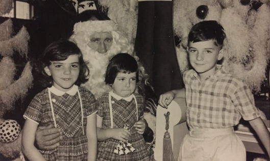Thee kids having photos with Santas in the 1960s